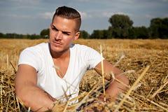 Man som sitter utomhus på ett höfält royaltyfri fotografi