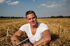 Man som sitter utomhus på ett höfält royaltyfria foton