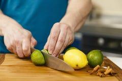 Man som skivar limefrukter och citroner Arkivfoto