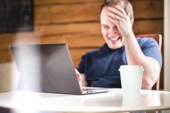 Man som skrattar, medan genom att använda bärbara datorn Lycklig le grabb med datoren royaltyfri fotografi