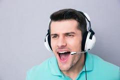 Man som skriker i hörlurar med mikrofon Arkivfoton