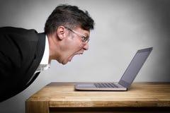 Man som skriker på bärbara datorn Royaltyfri Bild