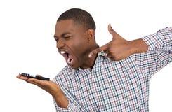 Man som skriker på någon på telefonen arkivbild
