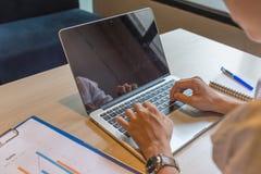 Man som skriver bärbara datorn bredvid anteckningsboken och dokumentet på arbetsplatsen royaltyfri foto