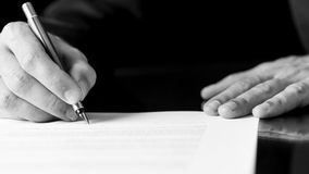 Man som skriver eller undertecknar ett dokument Royaltyfri Foto
