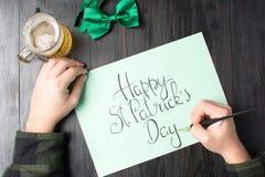 Man som skriver ett lyckligt St Patrick dagkort Royaltyfri Fotografi