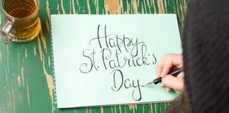 Man som skriver ett lyckligt St Patrick dagkort Arkivfoto