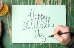 Man som skriver ett lyckligt St Patrick dagkort Arkivfoton
