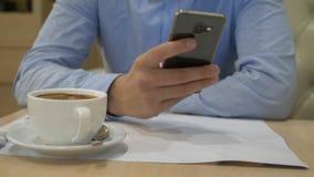 Man som skriver in ett meddelande genom att använda en mobiltelefon i ett kaffehus N?rbild 4K stock video