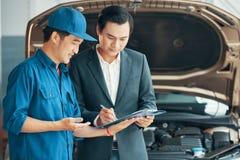 Man som skriver in in i ett avtal med en bilservice royaltyfri fotografi
