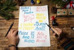 Man som skriver lyckligt nytt år i olika språk arkivfoto