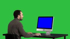 Man som skriver på datoren på en grön skärm, chromatangent Blue Screen modellskärm arkivfilmer