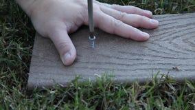 Man som skruva av en skruv från trä stock video