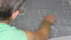 Man som skurar ett duschgolv arkivfilmer