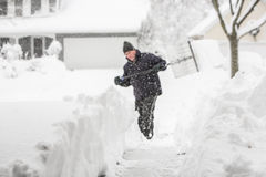 Man som skyfflar grunt djup för snö av fältet, fokus på insnöat för royaltyfri fotografi