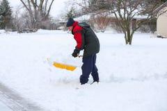 Man som skyfflar snö Arkivfoton