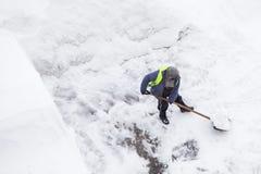 Man som skyfflar snö efter snöfall och häftiga snöstormen, kopieringsutrymme Bästa sikt av snörensning fotografering för bildbyråer