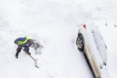 Man som skyfflar snö nära bilen på parkering Top beskådar royaltyfri bild