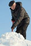 Man som skyfflar snow från en väg arkivfoto