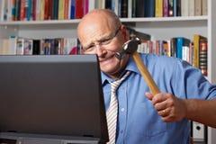 Man som slår datoren med hammaren arkivbilder