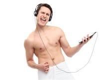 Man som slås in i handduken som lyssnar till musik Arkivbild