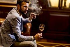 Man som smakar vitt vin och röker cigarren fotografering för bildbyråer