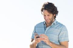Man som smsar på telefonen Royaltyfri Foto