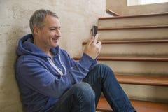 Man som smsar på telefonen Tillfällig stads- yrkesmässig entreprenör som använder att le för smartphone som är lyckligt arkivfoton