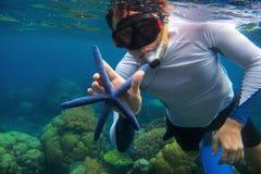 Man som snorklar i blått vatten med stjärnafisken korallrev som snorkeling Blå sjöstjärna för snorkelhåll Royaltyfri Bild