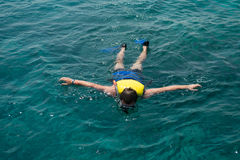 Man som snorklar i vatten med flytvästen Royaltyfri Bild