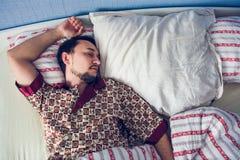 Man som sover i hans säng på den vita kudden Arkivbilder