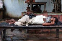 Man som sover i Varanasi Indien royaltyfri foto