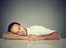 Man som sover på ett skrivbord arkivbilder
