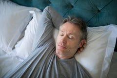 Man som sover på säng i sovrum Royaltyfri Foto