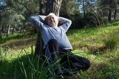 Man som sover under ett träd arkivbild