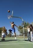 Man som spelar basket på domstolen medan vänner som ser honom Royaltyfri Foto