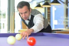 Man som spelar billiard i biljardhall Arkivbilder