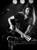 Man som spelar den akustiska gitarren på etapp Royaltyfri Bild