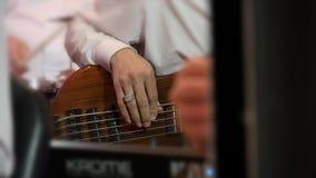 Man som spelar den Bass Guitar direkt konserten closeup arkivfilmer