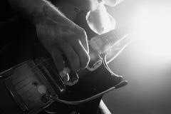 Man som spelar den elektriska gitarren i svartvitt Arkivfoton