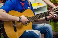 Man som spelar den förstärkta akustiska gitarren fotografering för bildbyråer
