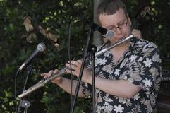 Man som spelar en flöjt på en festival arkivbilder