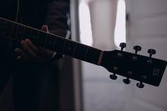 Man som spelar f?r gitarr closeupen inomhus p? fotoet royaltyfri foto