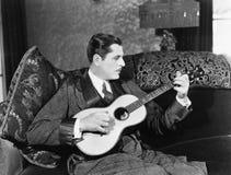 Man som spelar gitarren (alla visade personer inte är längre uppehälle, och inget gods finns Leverantörgarantier att det inte ska Arkivbild