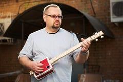 Man som spelar gitarren för cigarrask Royaltyfria Bilder