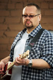 Man som spelar gitarren för cigarrask Royaltyfria Foton