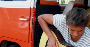 Man som spelar gitarren i campareskåpbilen 4k stock video