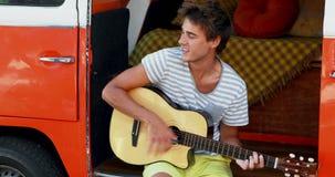 Man som spelar gitarren i campareskåpbilen 4k arkivfilmer