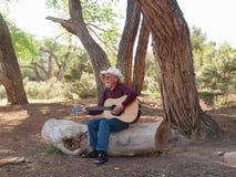 Man som spelar gitarren i ett ökenläger Arkivbilder