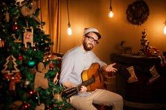 Man som spelar gitarren i julafton Arkivbild